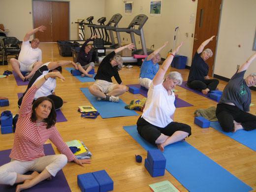 9 people sitting on yoga mats stretching