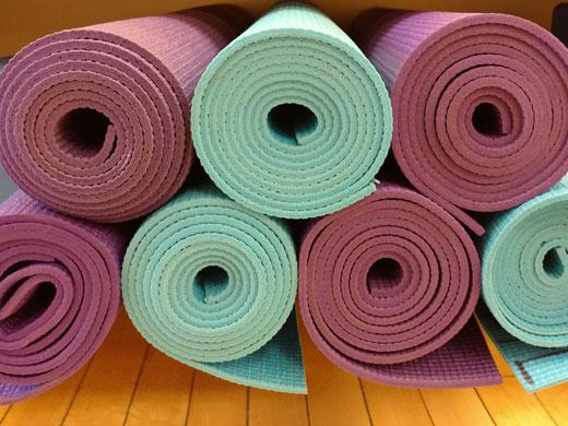 stack of rolled-up yoga mats