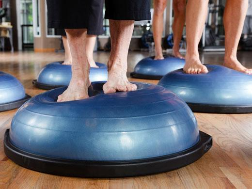 several people's feet balancing on exercise balls