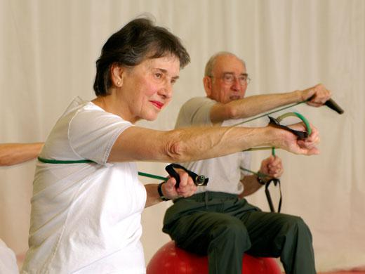 people extending their arms forward while holding elastic bands